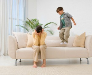A frustrated mom sitting next to her son who is jumping on the couch.