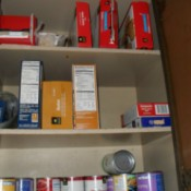 Closeup of shelves with boxes on top shelf lying on their sides.