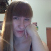 Girl with honey blond hair with bangs looking at the camera.