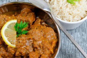 Lamb curry in a pan with a side of white rice.