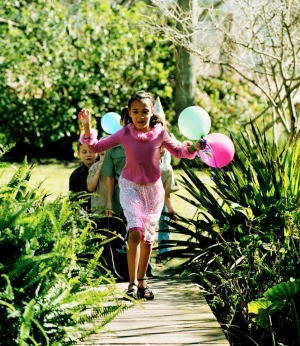 A birthday girl running with balloons in a garden.