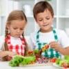 Two kids making fruit kabobs.