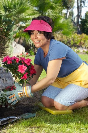 A woman gardening using a pad to keep her knees comfortable.