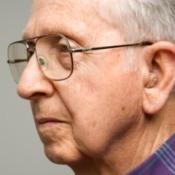 A senior man wearing a hearing aid.