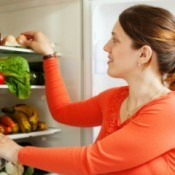 A woman looking in the refrigerator.