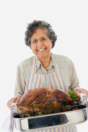 A woman holding a cooked turkey.