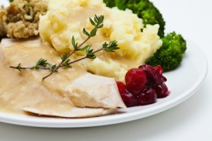 A plate of turkey dinner with turkey, cranberries and mashed potatoes.