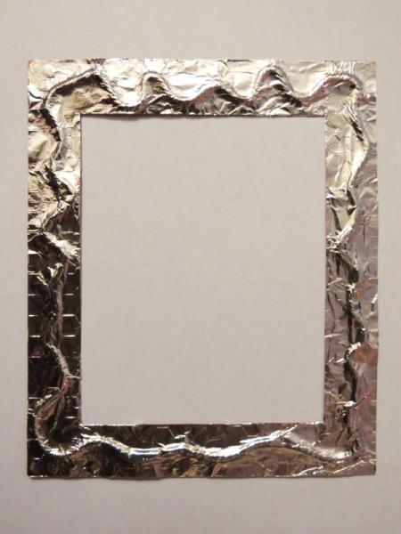 Foil glued to frame over twine.