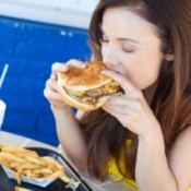 How to Get Grease Out of Fabrics - Woman eating a greasy hamburger