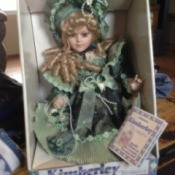 Doll dressed in green period clothing.