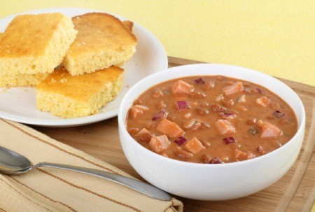 A bowl of ham and bean soup with corn bread.