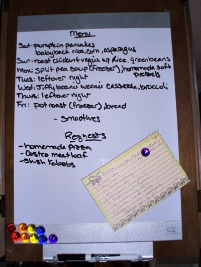White board being used to list a weekly dinner menu with an area for requests