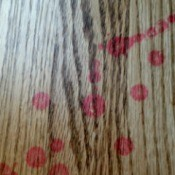 Red wax stains on wood floor.