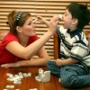 Teen Babysitter Playing Dominoes with Child