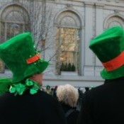 Two people watching a St Patrick's Day parade.