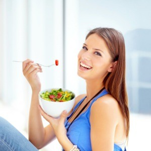 A happy woman eating a salad.
