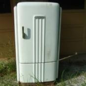 Old worn white metal refrigerator.