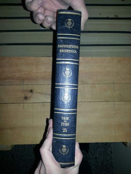 Someone holding up a volume to show the spine of the book.
