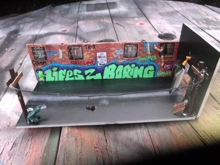 This handmade diorama is an urban street scene with telephone polls, brick walls with windows and graffiti.