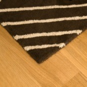 A rug sitting on a wood floor.