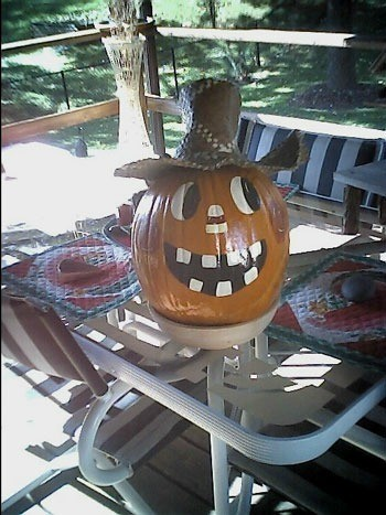 Decorated pumpkin on patio table.