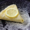 Making Crepes - Triangular folded crepe sprinkled with sugar and topped with a lemon slice.