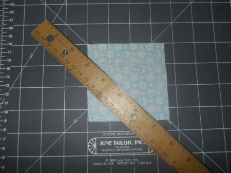 Fabric square on cutting mat with ruler.