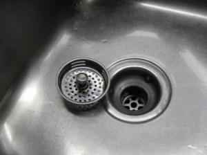 Drain strainer sittling next to drain in clean sink.