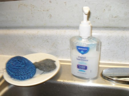 Pump soap and cleaning pad on back of sink.