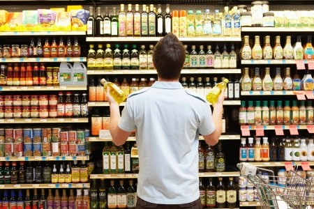 A man looking at a rack of different types of oil at a supermarket.