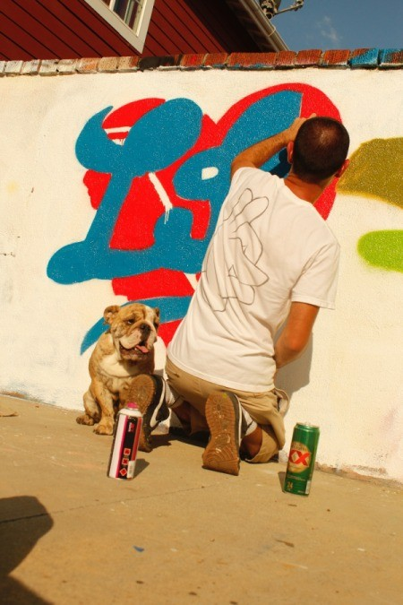 Sitting next to man painting a mural.