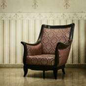 An antique chair in a room with expensive looking wallpaper.