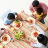 Family Eating Dinner on Table with Linen