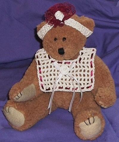 Teddy bear wearing bib and headband.