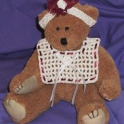 Teddy bear wearing bib and headband.