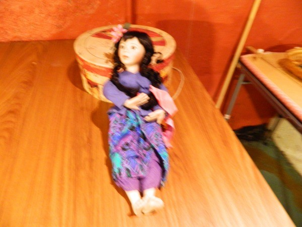 Female doll with blue and purple pants and wrap skirt.