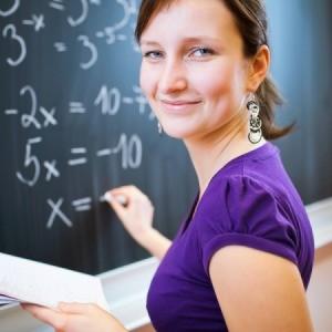 A math teach writing on a chalk board.