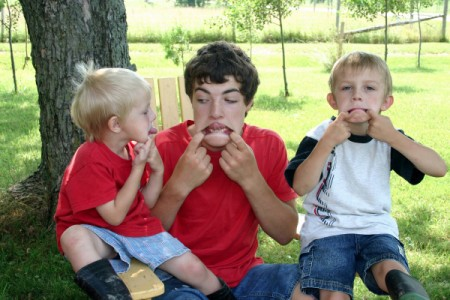 Older boy and two younger boys making faces.