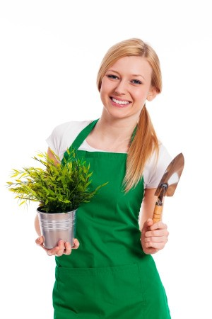 A female gardener wearing a green apron.