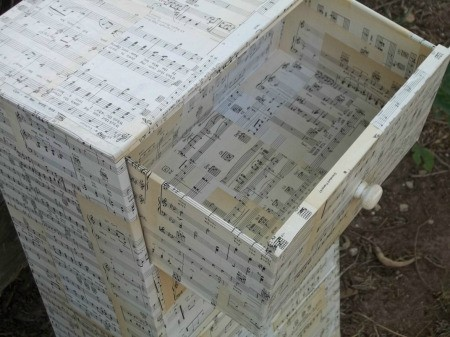 Decoupaging a dresser with old sheet music.