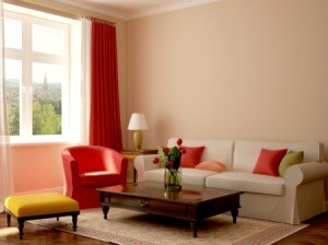A tan colored couch with colorful pillows.