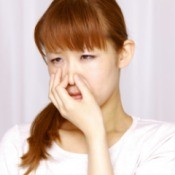 A woman holding her nose because of a bad smell.