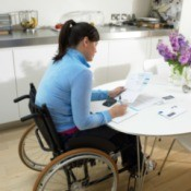 A woman sitting at table in a wheelchair.