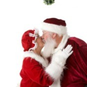 Santa and Mrs. Claus kissing under a kissing ball.