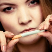 A girl breaking a cigarette in half.