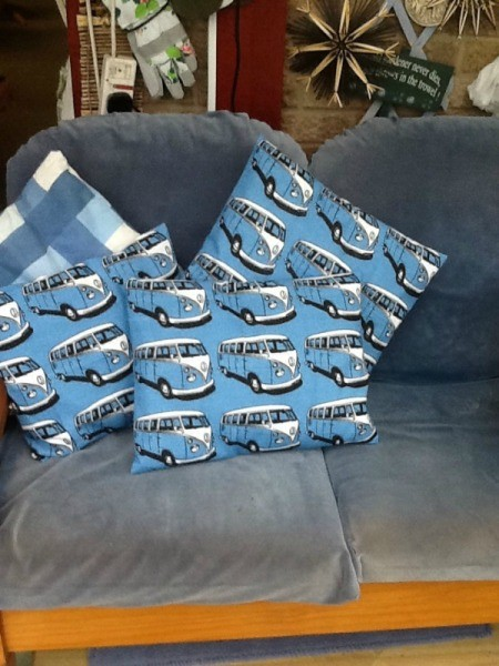Four cushions or throw pillows. Three have VW microbus motif and one is blue plaid.