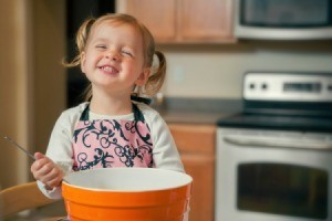 A young girl baking.