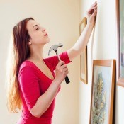 A woman hanging pictures on a wall.