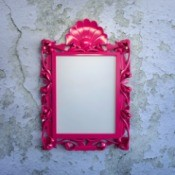 A picture frame on a plaster wall.