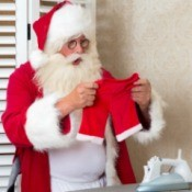 Santa looking at his pants that have been shrunk in the laundry.
